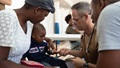 U.S. Navy Capt. Michael Sullivan, a pediatrician assigned to the hospital ship USNS Comfort, gives a sticker to a two-year-old boy after examining his skin infection at a temporary medical treatment site in Port-Au-Prince, Haiti. During Comfort's deployment, the crew worked with health and government partners in Central America, South America, and the Caribbean to provide care on the ship and at a temporary medical treatment site, helping to relieve pressure on national medical systems, including those strained by an increase in cross-border migrants. (U.S. Navy Photo by Mass Communication Specialist 3rd Class Maria G. Llanos)