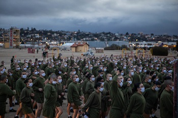 A large group of military personnel wearing face masks, listening to someone speak