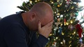 Man with his head in his hands, sitting in front of a Christmas tree