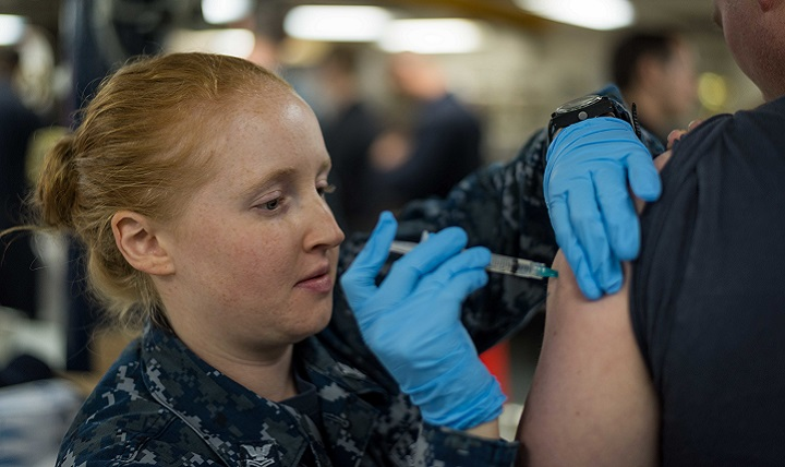 Navy Hospital Corpsman 2nd Class Carly Marcum, administers an influenza vaccination to a Sailor aboard USS John C. Stennis. This flu season, the DoD's entire supply of flu vaccine will be injectable. (U.S. Navy photo by Mass Communication Specialist Seaman Cole C. Pielop)