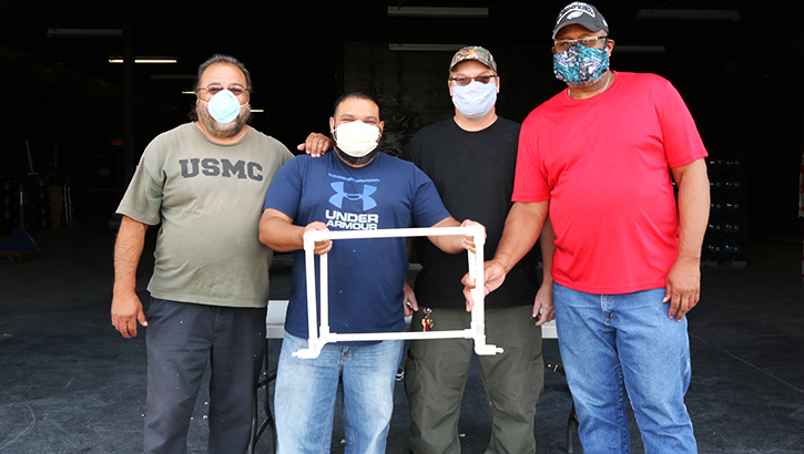 Four men wearing masks, holding COVID-19 Airway Management Isolation Chamber