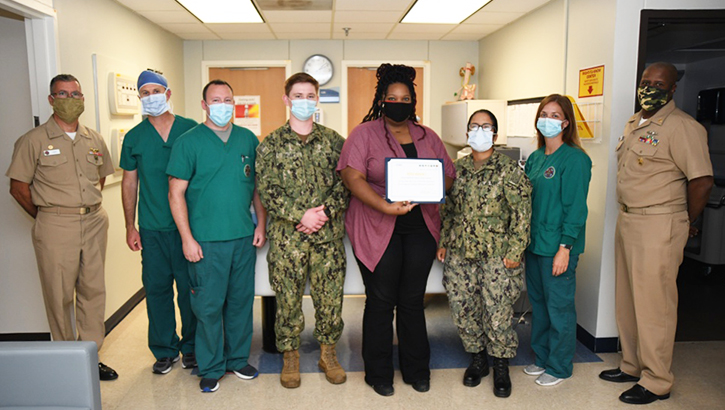 Naval Medical Center Camp Lejeune staff stand with award from the Joint Outpatient Experience Survey.