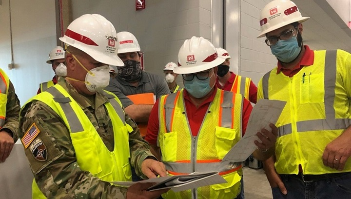 Image of three men in construction gear standing around plans