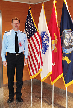 Image of man standing next to four flags