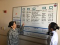 Lt. Col. Laura Lewis points to the whiteboard as she speaks with Maj. Jill Hibbert about action items on the leadership daily management board. The 61st Medical Squadron at the Los Angeles Air Force Base discuss uses the boards to track information shared during huddles to improve visibility and accountability.