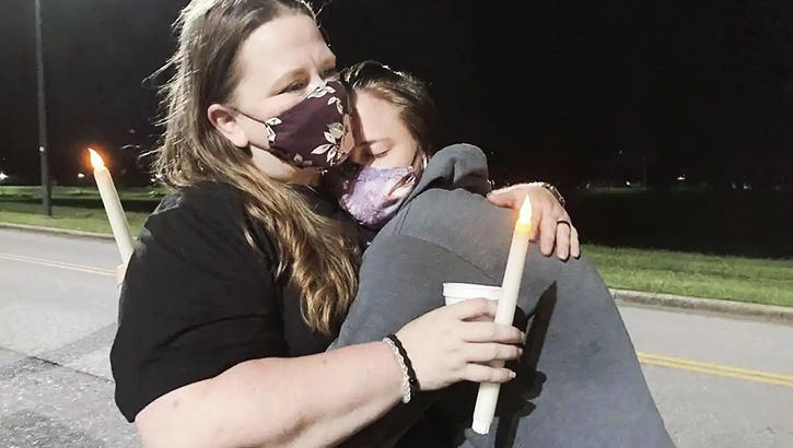 Woman wearing a mask, hugging her daughter