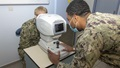 military health personnel wearing a mask and performing an eye exam