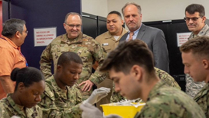 Air Force Maj. Gen. Lee Payne, Defense Health Agency's assistant director for combat support and Military Health System, GENESIS Functional Champion, and William J. Tinston (center), Defense Healthcare Management System's program executive officer, tour Marine Corps Recruit Depot San Diego's Naval Branch Health Clinic and observes hospital corpsman sort injections Oct. 2. (U.S. Navy photo by Mass Communication Specialist 3rd Class Jake Greenberg)