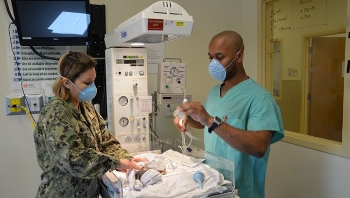 Two medical personnel with a simulated baby in a medical setting