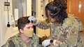 Military health personnel wearing face mask practicing using an EEG