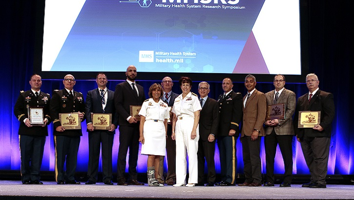 Navy Vice Adm. Raquel C. Bono and Navy Rear Adm. Mary C. Riggs join individual and team award winners honored at the 2019 Military Health System Research Symposium on Monday, August 19th in Kissimmee, Florida. (MHS photo)