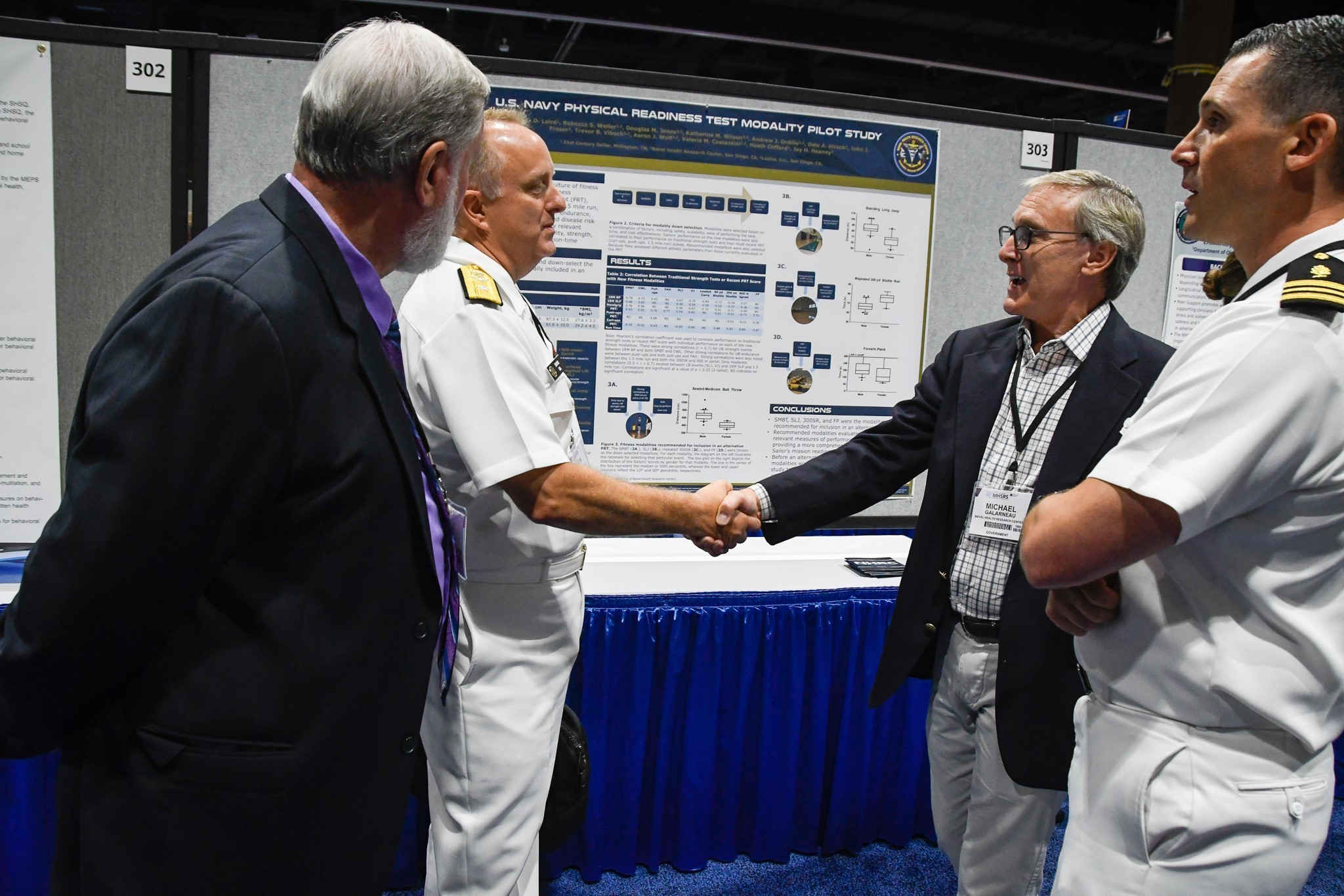 Navy Rear Adm. Darin K. Via, deputy chief, Readiness and Health, Bureau of Medicine and Surgery, meets with Mr. Mike Galarneau, director, Operational Readiness & Health, Naval Health Research Center, during poster presentations while attending MHSRS 2019. (U.S. Navy photo by John Marciano)