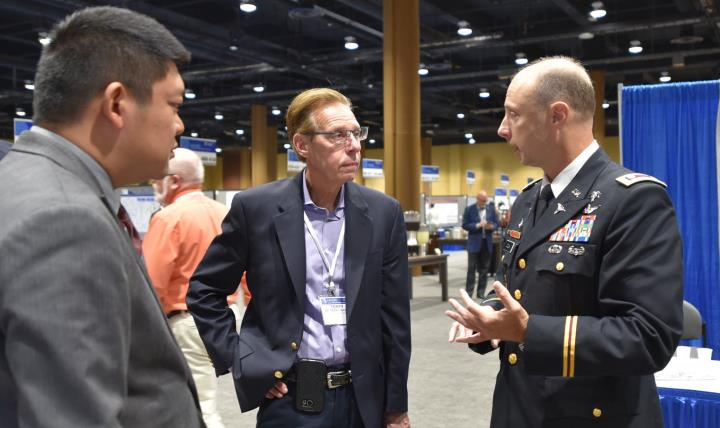 Dr. Terry Rauch (center), acting deputy assistant secretary of Defense for Health Readiness Policy and Oversight, chats with fellow attendees of the Military Health System Research Symposium, just completed in Kissimmee, Florida. (Photo: Greg Pugh, U.S. Army Medical Materiel Agency)
