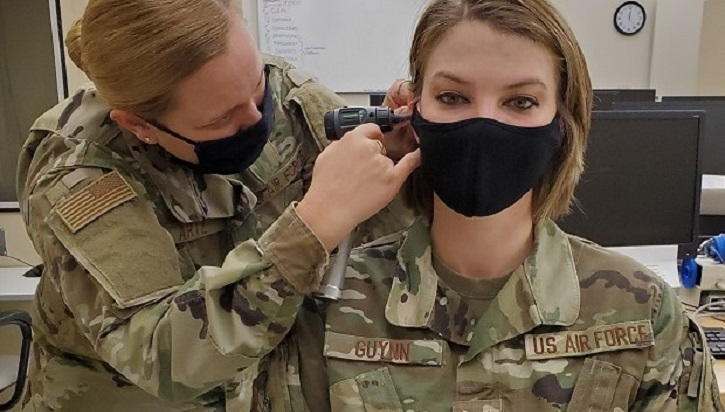 Military doctor inspecting patient's ear