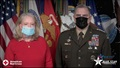 Mr. and Mrs. Milley, wearing masks, standing in front of various flags.
