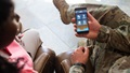 Soldier holding cell phone, showing app to another person
