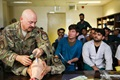 Navy Lt. Cdr. Travis J. Fitzpatrick, senior nurse for Kandahar Airfield NATO Role III Multinational Medical Unit, demonstrates a technique on how to clear the airway of a patient to Afghan medical staff members during a medical advisory visit at Kandahar Regional Military Hospital, Camp Hero in Kandahar, Afghanistan. Staff members from the Role III conduct routine visits to KRMH to train and advise Afghan medical staff. (U.S. Army photo by Staff Sgt. Neysa Canfield)