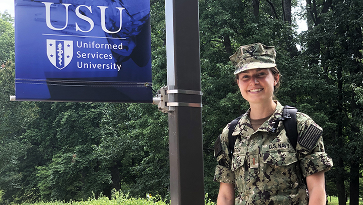 Military soldier standing next to a USU flag
