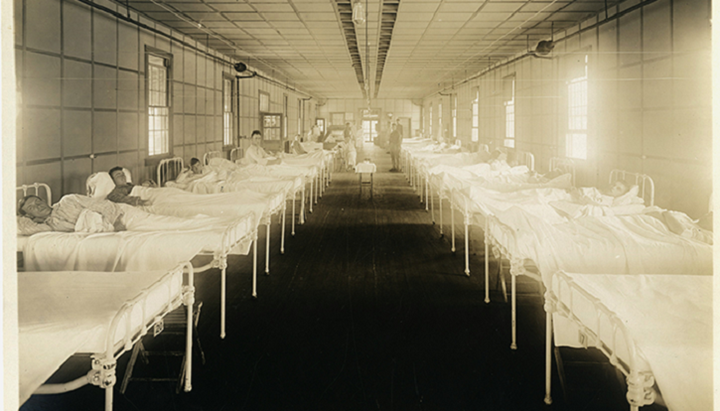 Image of two rows of empty hospital beds in the early 1900s