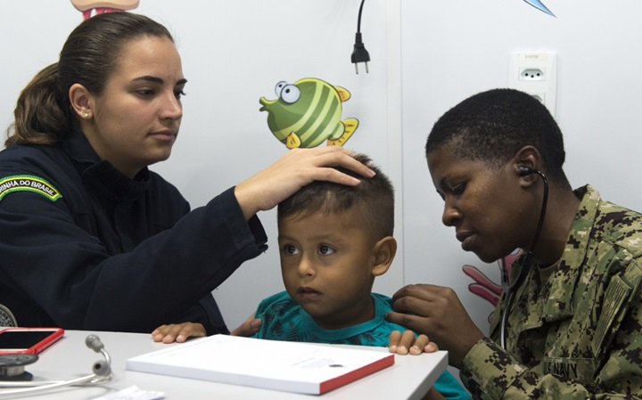 AMAZON RIVER, Brazil (Nov. 21, 2017) Lt. Cmdr. Nehkonti Adams, an infectious diseases specialist, works with 2nd Lt. Raissa Vieira Sanchez, a Brazilian medical officer, to diagnose a small boy from a remote village along the Amazon River in Brazil, November 21. Adams is part of a team of five U.S. Navy doctors who are engaging in a month-long humanitarian mission up the Amazon River. The team is working with the Brazilian Navy to deliver healthcare to some of the most isolated people in the world. (U.S. Navy photo by Mass Communication Specialist 2nd Class Andrew Brame/Released)