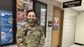 Military personnel wearing a face mask standing in front of a Nutrition Clinic