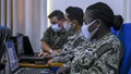 Picture of military personnel wearing a face mask looking at a laptop computer
