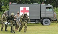 Japan Ground Self-Defense Force medics carry a casualty from an ambulance to a JGSDF helicopter while a U.S. Army medic calls directions during a bilateral medical training exercise.