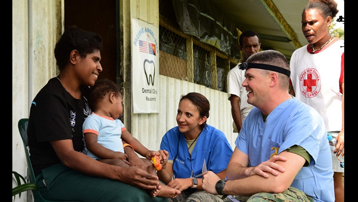 Navy Lt. Austin Stokes, (right), and Air Force Maj. Nicole Smith (center), both dentists, talk to a patient at the Pacific Angel 19-4 health outreach site in Lae, Papua New Guinea. The health outreach site is comprised of five clinics including primary care, optometry, dental, physical therapy and pharmacy. (U.S. Air Force photo by Staff Sgt. Jerilyn Quintanilla)
