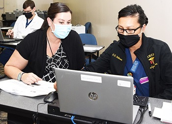 Military health personnel looking at a laptop computer screen