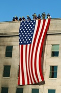 Military Service members render honors as fire and rescue workers unfurl a huge American flag over the side of the Pentagon during rescue and recovery efforts following the Sept 11 terrorist attack. The attack came at approximately 9:40 a.m. as a hijacked commercial airliner, originating from Washington D.C.'s Dulles airport, was flown into the southern side of the building facing Route 27. (U.S. Navy photo by Photographer's Mate 1st Class Michael W. Pendergrass)