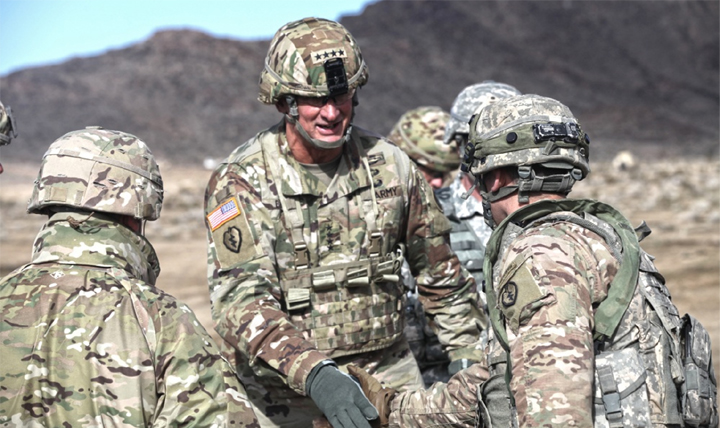 A career spent in the infantry coupled with an active lifestyle led to 12 knee surgeries for U.S. Army Gen. Robert B. Brown, Commanding General of U.S. Army Pacific. Shown here (center) greeting soldiers at the National Training Center Fort Irwin, Calif., Brown credits an effective physical therapy regimen for getting him back in the field. (U.S. Army Sgt. Michael Spandau)