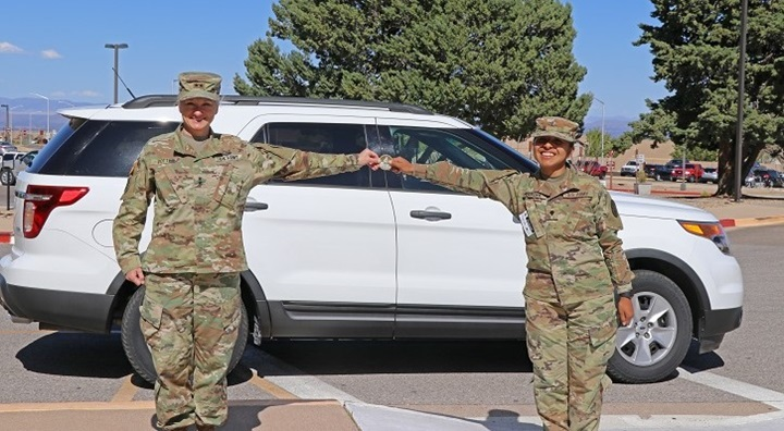 Two soldiers standing in front of a car, holding a coin