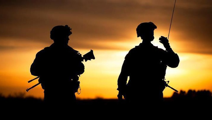 Sunset light creates silhouette of two military personnel