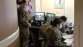 Military personnel standing and sitting at a desk with multiple computer screens