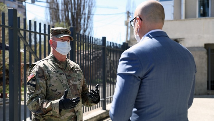 Two men (one in uniform, one not) with face masks having a discussion