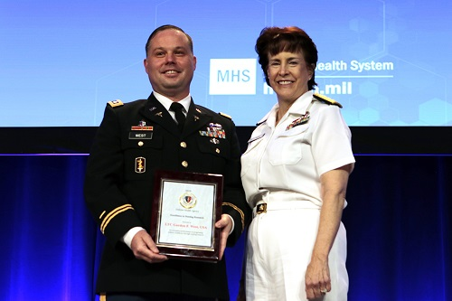Army Lt. Col. Gordon West, a nurse scientist at Tripler Army Medical Center in Hawaii received the inaugural Captain Anita C. Bacher Award for Excellence in Military Nursing Research. Navy Rear Adm. Mary C. Riggs, deputy assistant director, research and development at the Defense Health Agency, presented the award on Monday, August 19th at the 2019 Military Health System Research Symposium on Monday, August 19th in Kissimmee, Florida. (MHS photo)