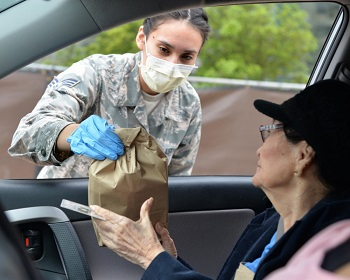 Female soldier wearing a mask handing a bag to a woman in a car