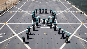 Military personnel for a teal ribbon on a flight deck