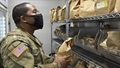 Military pharmacist, wearing a mask, looking at bags of prescriptions
