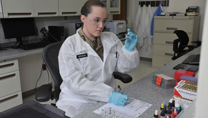 Scientist looking at samples in test tubes in a lab.