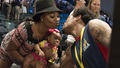 Man at sporting event kissing his wife and baby