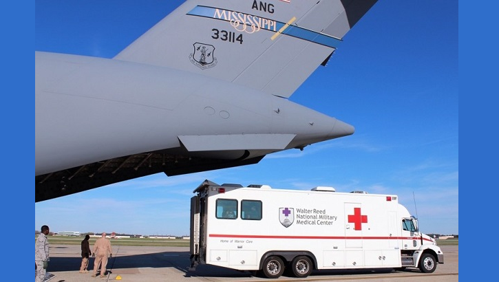 An ambulance bus backs up to the Mississippi Air National Guard C-17 Globemaster III as Airmen prepare to unload patients at Joint Base Andrews, Maryland. The bus transports the ill and/or injured to Walter Reed National Military Medical Center in Bethesda, Maryland. JBA and Travis Air Force Base, California, serve as the primary military entry points or hubs for patient distribution within the continental United States. (U.S. Air Force photo by Karina Luis)