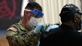 Military health personnel wearing a face mask and a face shield administering the COVID-19 vaccine