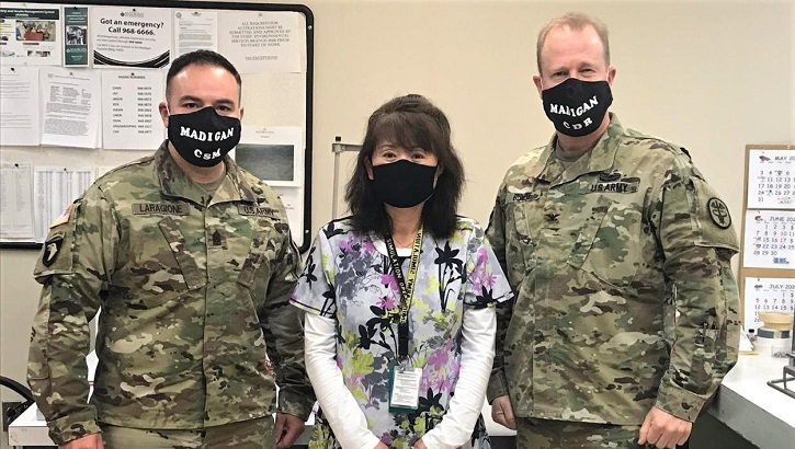 Three military personnel wearing masks