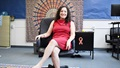 Woman in red dress sitting on chair and posing for the camera
