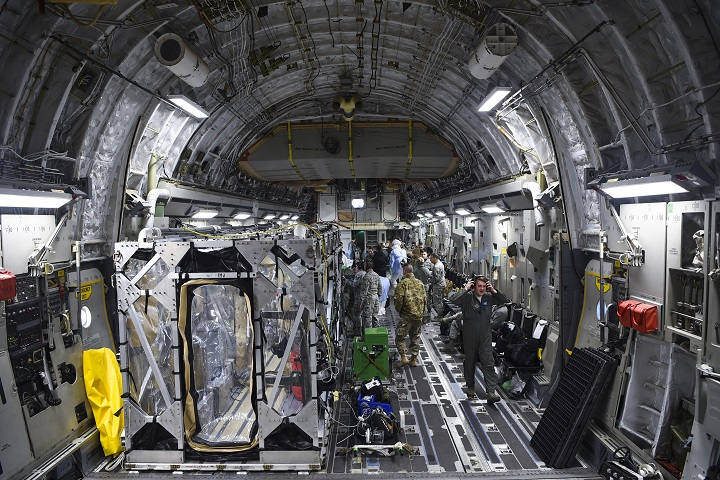 A C-17 Globemaster III is prepped to transport a Transportation Isolation System during a
