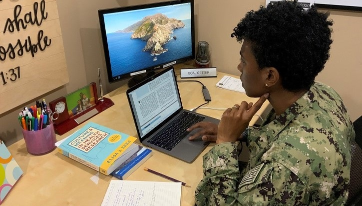 Image of soldier sitting at desk looking at laptop