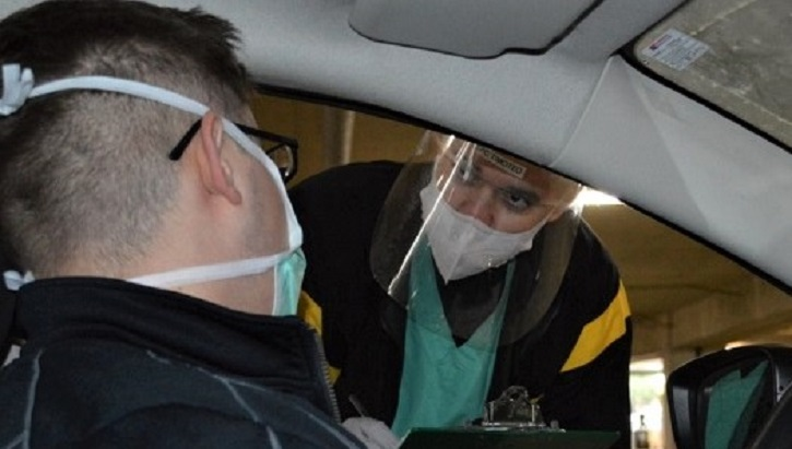 Two men wearing masks, one in a car, one leaning in the car