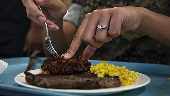 Woman cutting a steak on a plate, with corn