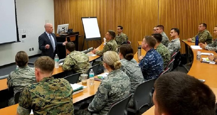 Instructor at front of class, speaking to military students